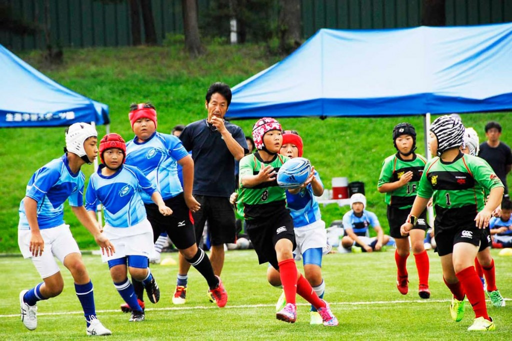 ミニゲームで交流する東大阪ラグビースクール(青)と釜石シーウェイブスジュニア(緑)の子どもたち